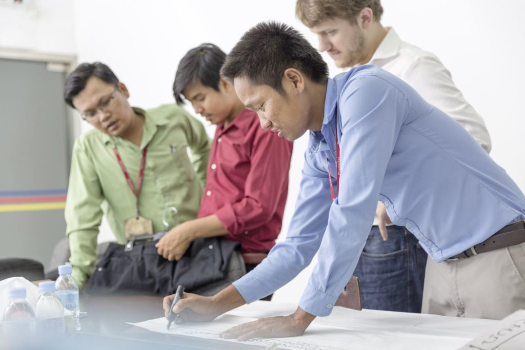 Four men bend over a table on which one of them is writing something
