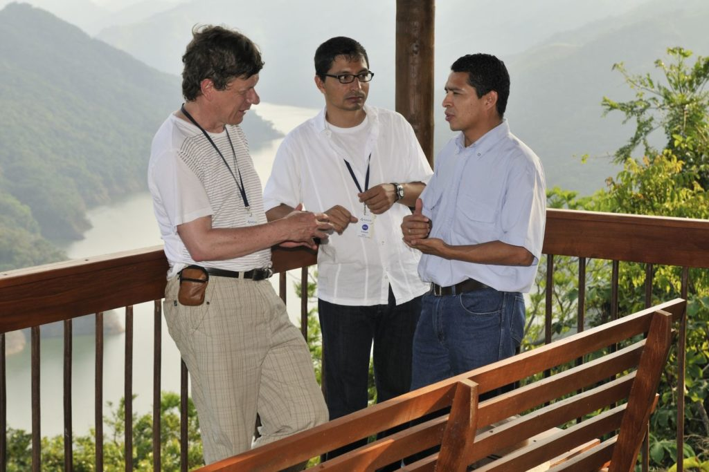 Three men discussing outside