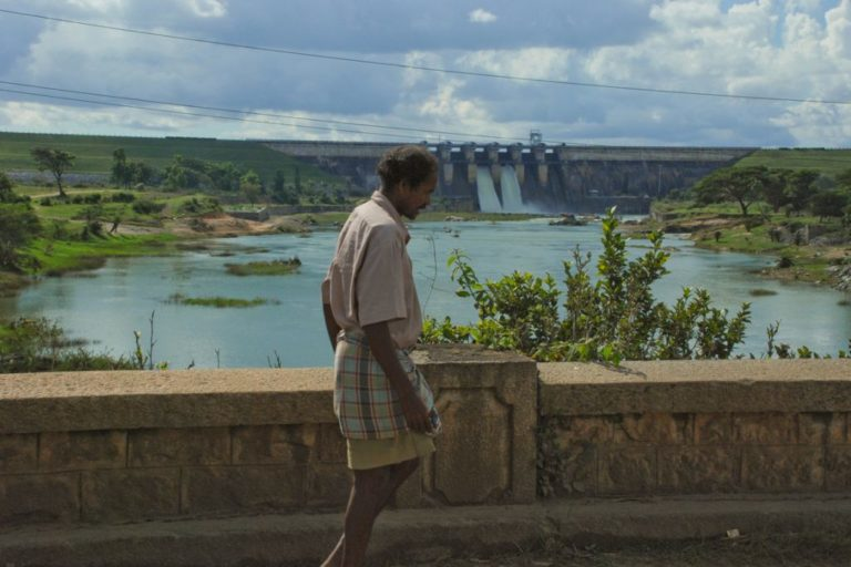 A man in front of a dam